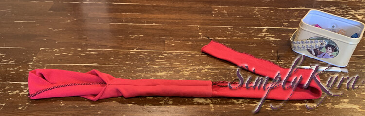 Image shows the band folded in half with the longer end going through the opening and out then other end.