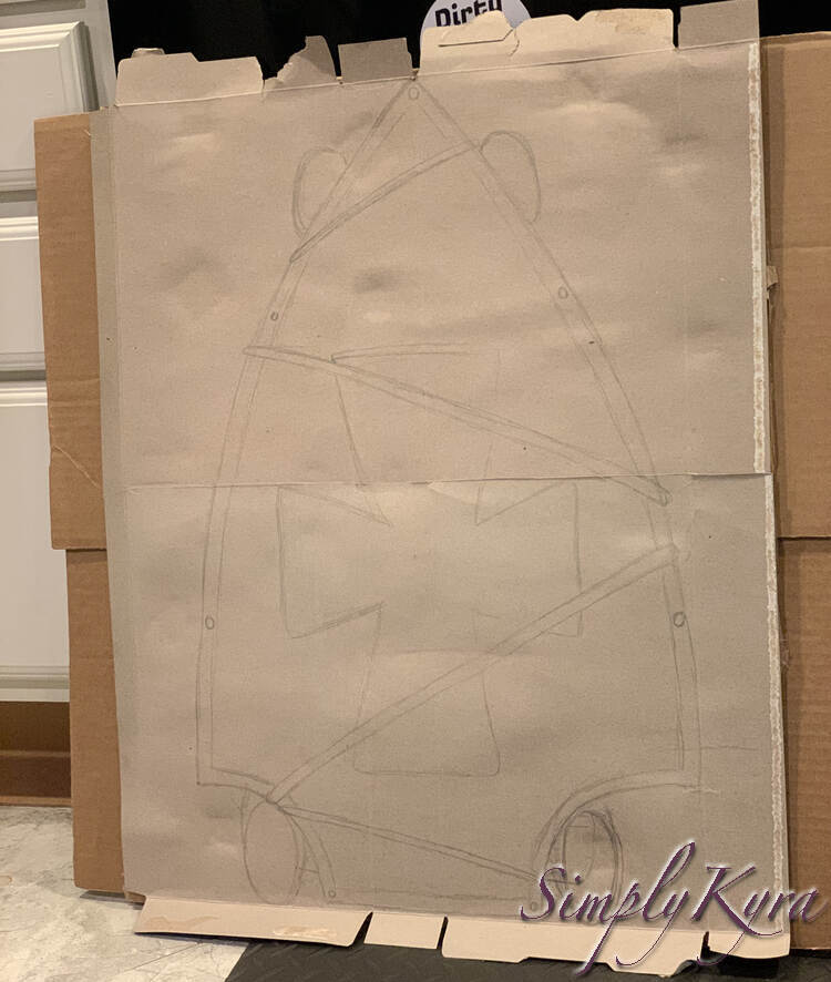 Image shows the cardboard leaned up against my cupboards on the kitchen floor. On it you can see the skateboard sketched out showing the shield shape, it's details, the four wheels, and the lines were the necklace was used to attach them together.