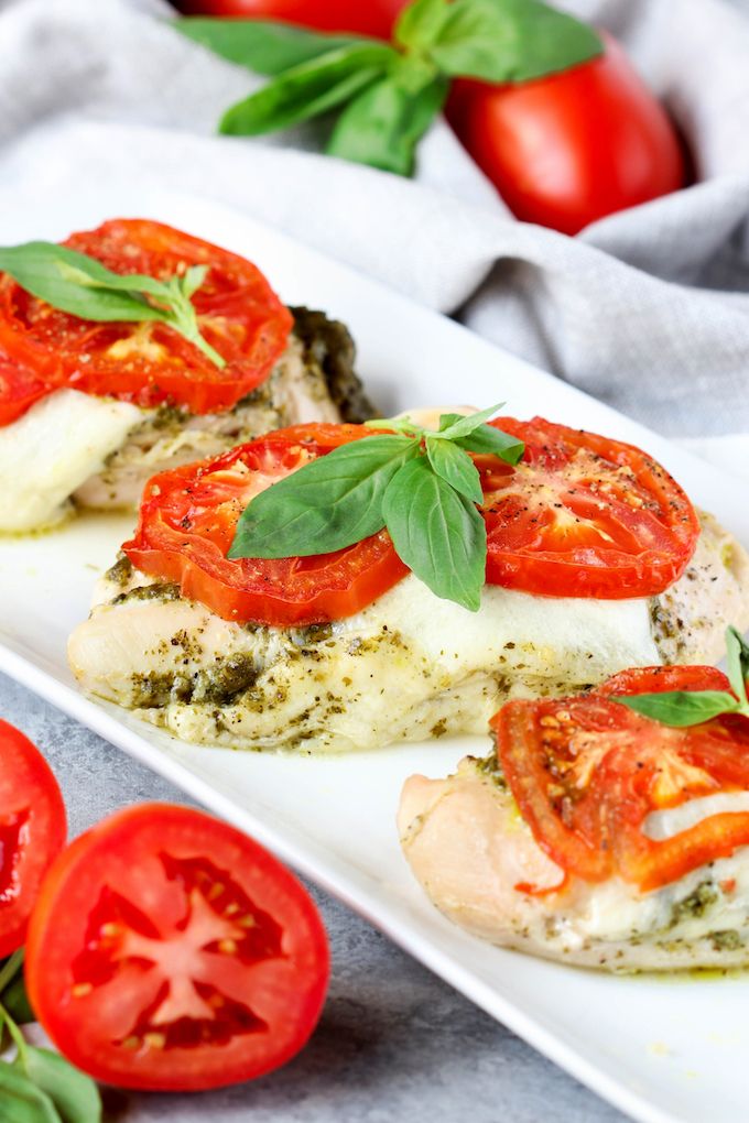 4 Ingredient Pesto Chicken Bake is healthy, simple,delicious and requires just 5-minutes prep. Juicy chicken topped with fresh pesto, melty mozzarella and topped with vine ripened tomatoes.