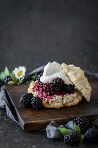 rustic blackberry shortcake on wood board with blackberries as garnish