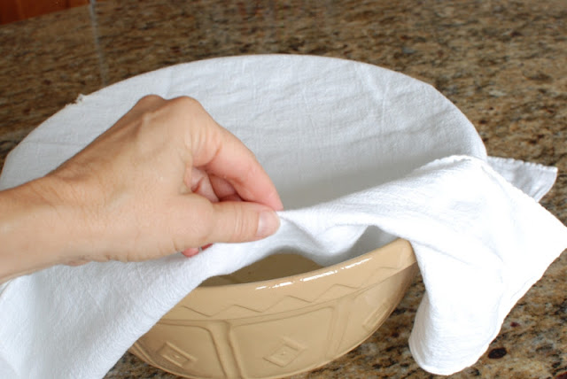 White cloth covering rising dough in large bowl