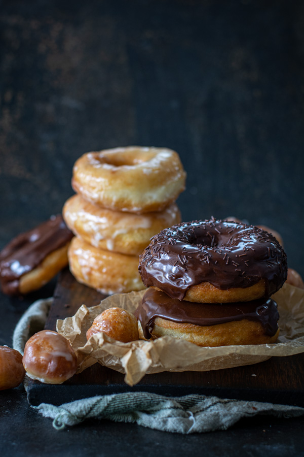 chocolate glazed and glazed spudnuts stacked on cutting board with donut holes