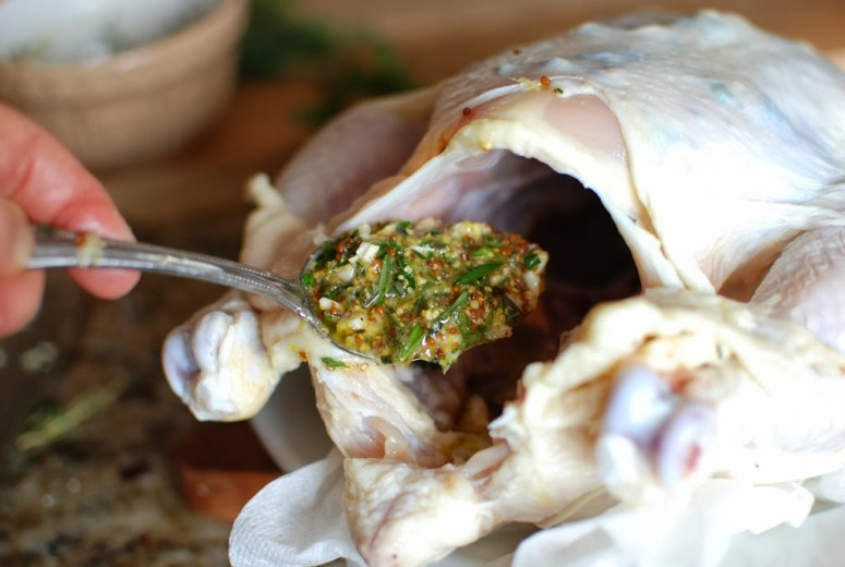 herb garlic sauce spooned into cavity of chicken