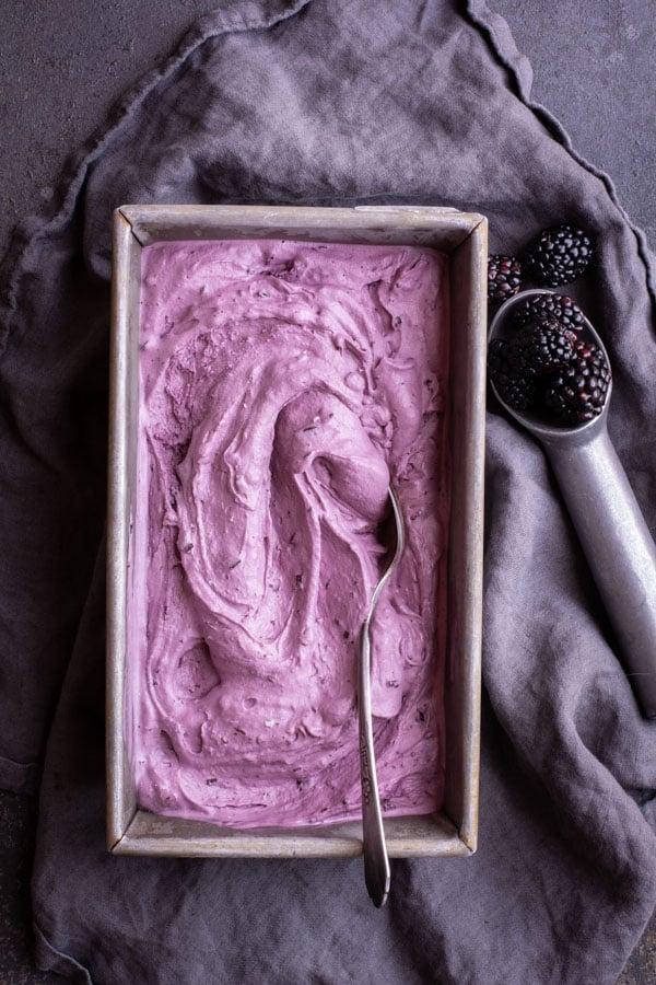 rectangular bread pan with ice cream on dark gray cloth with Blackberry Chocolate Chip ice cream scoop and blackberries
