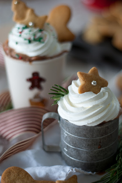 silver mug and cup with whipped cream small star gingerbread cookies red striped ribbon