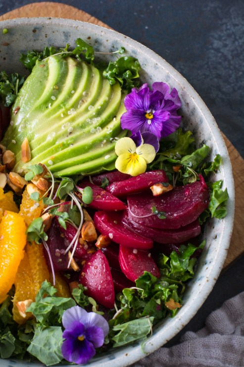 Avocado slices, beets, fruit, pansies on kale
