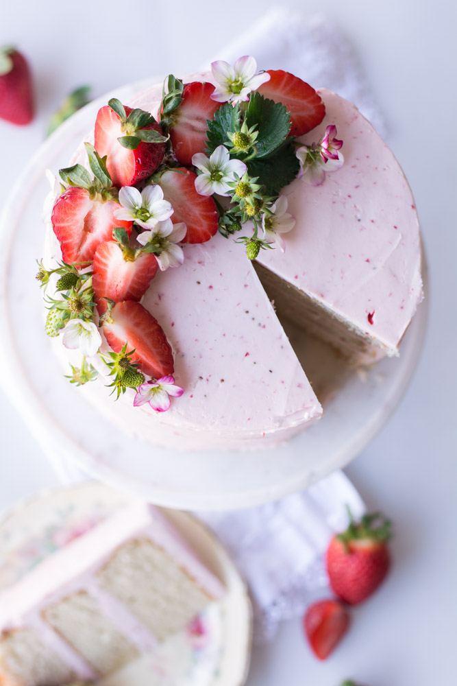 overhead shot of strawberry iced cake with strawberries on top