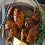 Grilled Huli Huli Chicken on a wooden platter with fresh herbs and pineapple wedges