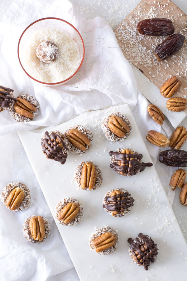 Pecans on date bites on platter with drizzled chocolate