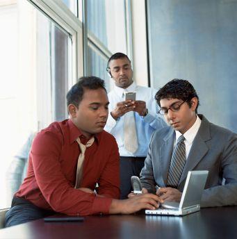 Businessmen using electronics