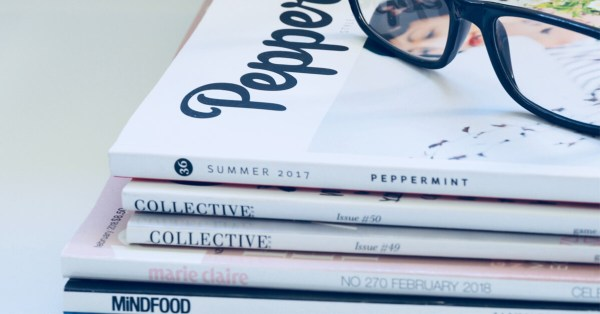 Stack of Magazines with Glasses Resting on Top