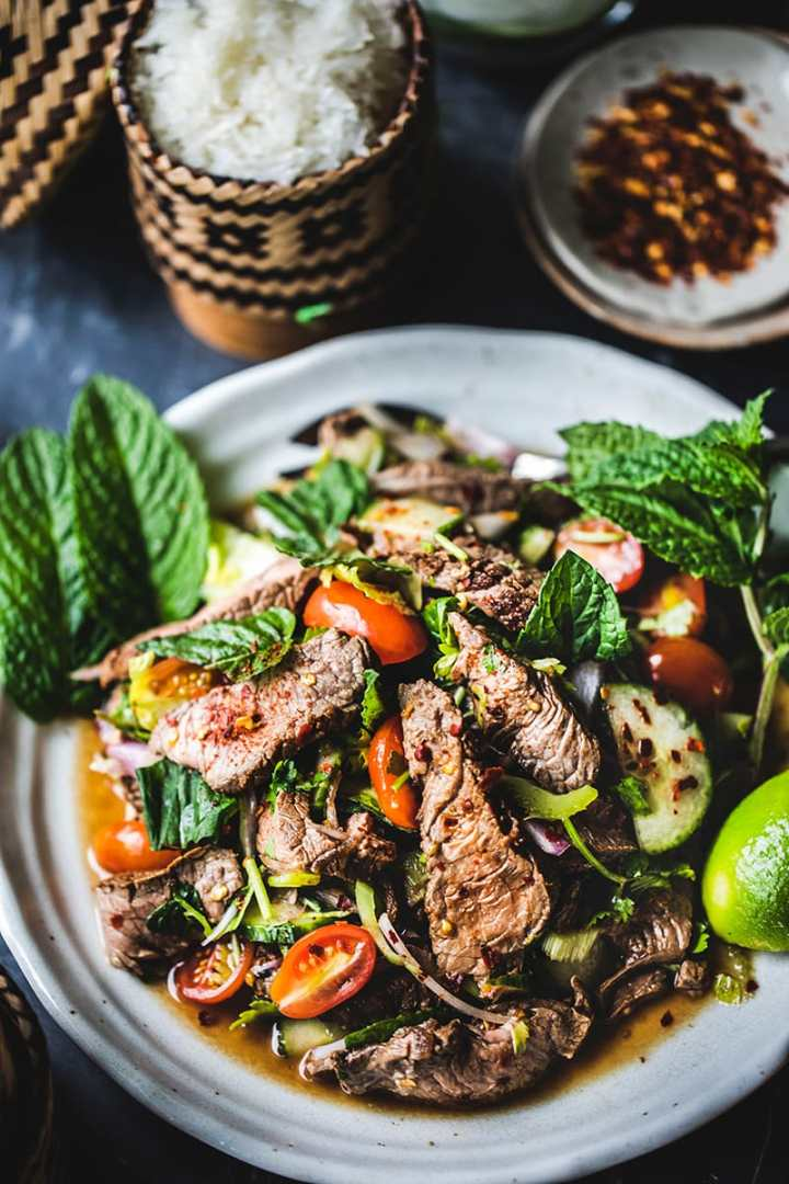 A simple recipe for Thai beef salad made with fresh summer vegetables, herbs, lime juice, and fish sauce. Once you gather all your ingredients for this Thai beef salad recipe, you'll be eating a tasty meal in less than 30 minutes (minus the marinating part)!  #thaibeefsalad #easybeefsaladrecipe #thaisaladrecipe #spicysaladrecipe