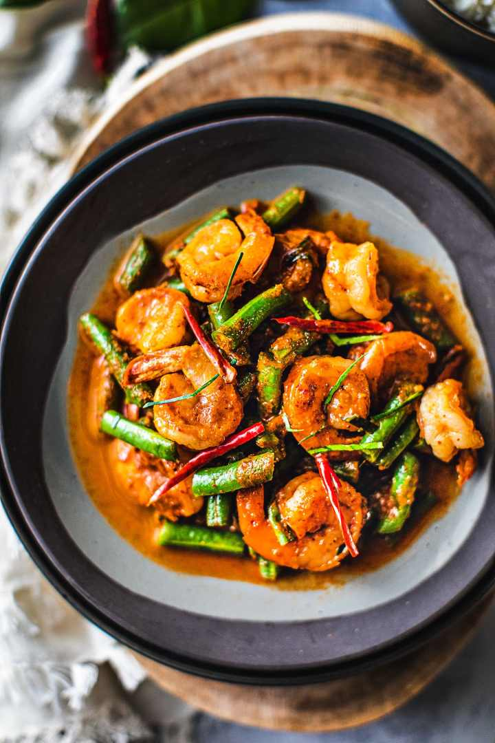 This easy red curry green beans with shrimp, or Pad Prik King, is a simple and delicious Thai dish that lightly fries red curry paste together with coconut cream, shrimp, kaffir lime leaves, and green beans. #redcurry #shrimpcurry #thaifood #thairedcurrry