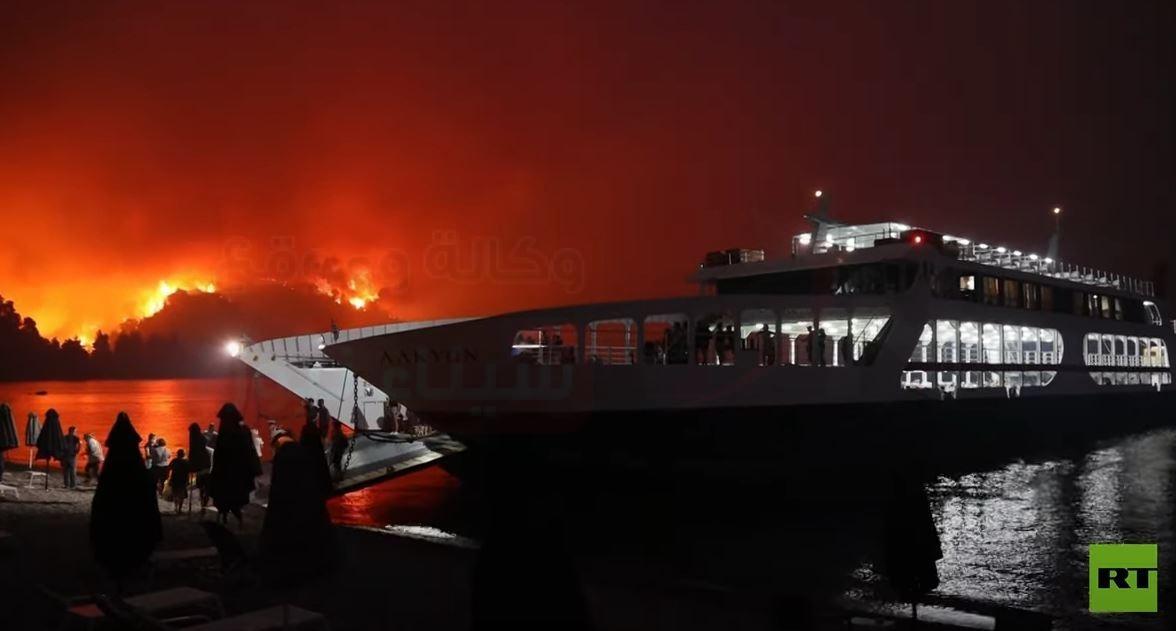فيديو.. سفينة تُجلي المئات عبر البحر مع اقتراب الحرائق من جزيرة يونانية