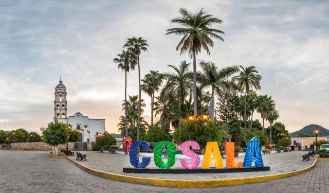 Plazuela de Cosalá y la Parroquia de Santa Ursula con unas letras grandes y coloridas sobre la banqueta que dicen: Cosalá