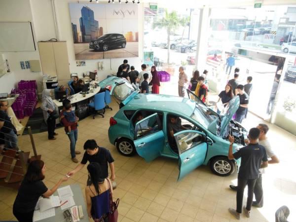 Pelanggan melihat model Perodua Myvi 1.3X di galeri pameran Perocom Auto.