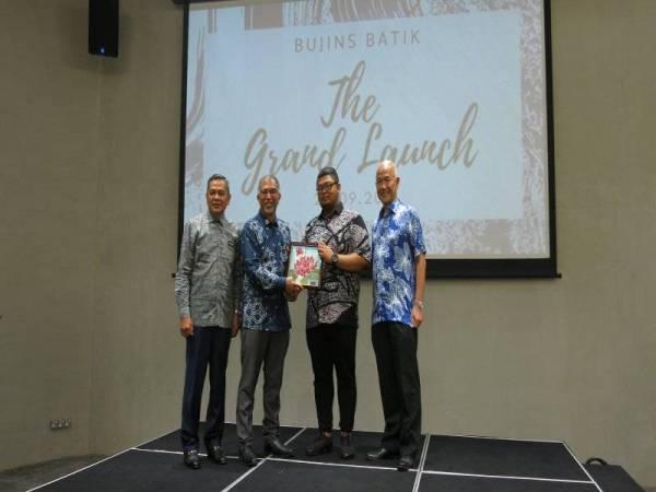 Amir Harith (dua dari kanan) menyampaikan cenderahati kepada Muhammad Bakhtiar diiringi oleh Ibrahim pada Majlis perasmian Pusat Jualan dan Galeri Bujins Batik di GM Bukit Bintang, Kuala Lumpur kelmarin.