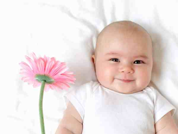 91280166 – baby girl holding a flower on her bed