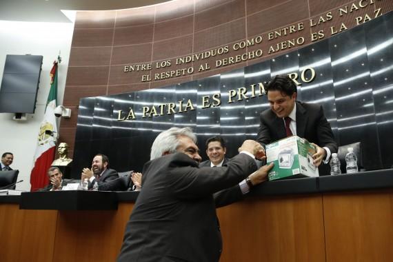 El Senador perredista Zoé Robledo le regala una televisión al priista José Orihuela. Foto: Cuartoscuro