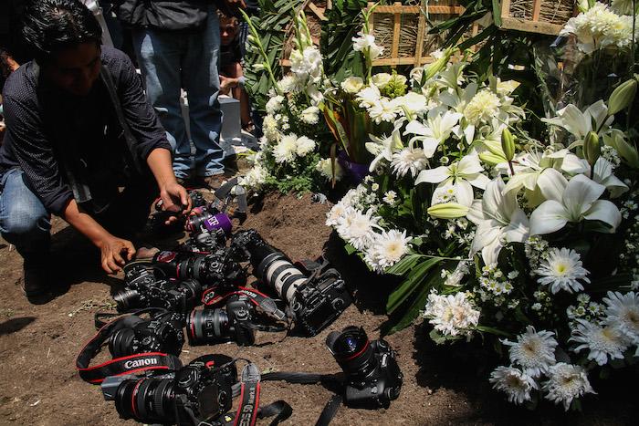 Los fotógrafos asistentes al entierro, cubrieron la tumba de Rubén con sus cámaras. Foto: Cuartoscuro