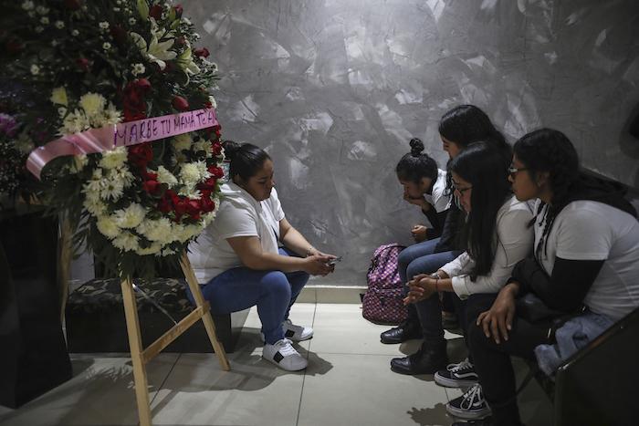 """Amigas de la mujer asesinada Marbella Valdez se sientan junto a una corona de flores con el texto """"Marbe, tu mamá te ama"""", junto a su ataúd durante el funeral en una funeraria de Tijuana, México, el jueves 13 de febrero de 2020. Foto: Emilio Espejel, AP"""