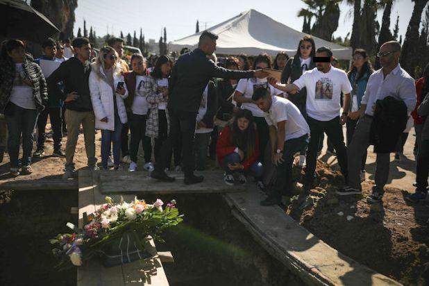 Un hombre llamado Juan, segundo por la derecha, que fue detenido en relación con la desaparición y el asesinato de Marbella Valdez, entrega un retrato de la víctima al ex novio de Valdez, Jairo Solano, junto a la hermana de la víctima, Brenda, arrodillada, y su padrastro, William H. Hessik, en el extremo a la derecha, durante el entierro en un cementerio de Tijuana, México, el viernes 14 de febrero de 2020. Foto: Emilio Espejel, AP