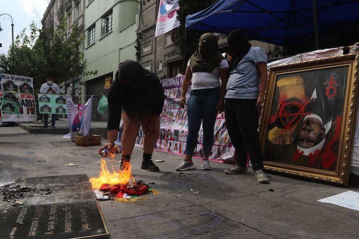 Mujeres feministas y madres de víctimas de violencia colocaron las pinturas intervenidas de los personajes históricos de cabeza para pedir subasta por ellos y quemaron una bandera durante el cuarto día de la toma de las instalaciones de la Comisión Nacional de Derechos Humanos (CNDH).