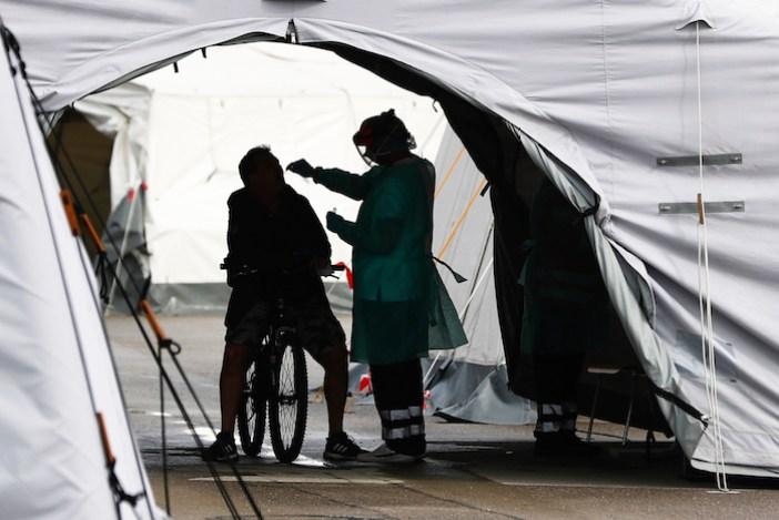 Una empleada de salud toma una muestra de un ciclista que se presentó como voluntario para una nueva prueba de coronavirus en la zona del Oktoberfest en Theresienwiese, el jueves 24 de septiembre de 2020 en Munich, Alemania.