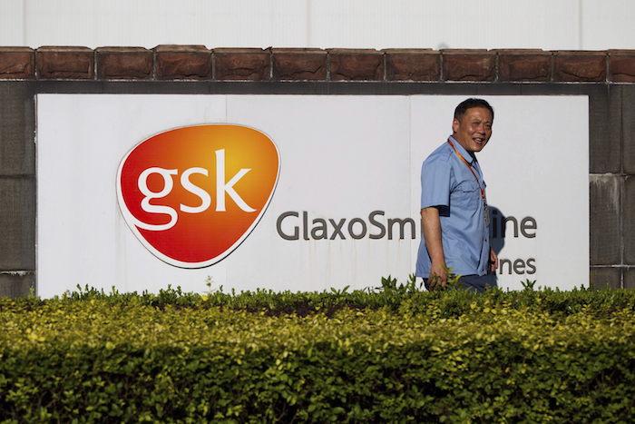 Un guardia de seguridad pasa junto al cartel de la farmacéutica británica GlaxoSmithKline (GSK).