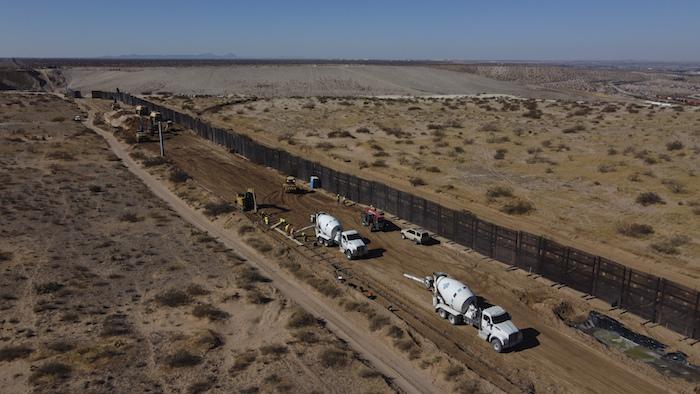 Una cuadrilla de trabajadores preparando los cimientos de una sección de acero del muro fronterizo que se construirá en el lado mexicano de una antigua valla metálica que separa Ciudad Juárez, México, de Sunland Park, Nuevo México, en las afueras de Ciudad Juárez, en esta fotografía del martes 12 de enero de 2021.