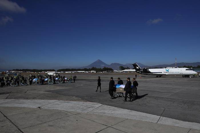 Los restos de 16 migrantes guatemaltecos que fueron asesinados cerca de la frontera entre Estados Unidos y México en enero llegan a la base de la Fuerza Aérea en Ciudad de Guatemala, el viernes 12 de marzo de 2021.
