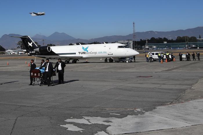 Personas transportan ataúdes cubiertos con banderas en la pista mientras los restos de 16 migrantes guatemaltecos que murieron cerca de la frontera entre Estados Unidos y México en enero llegan a la base de la Fuerza Aérea en la Ciudad de Guatemala, el viernes 12 de marzo de 2021.