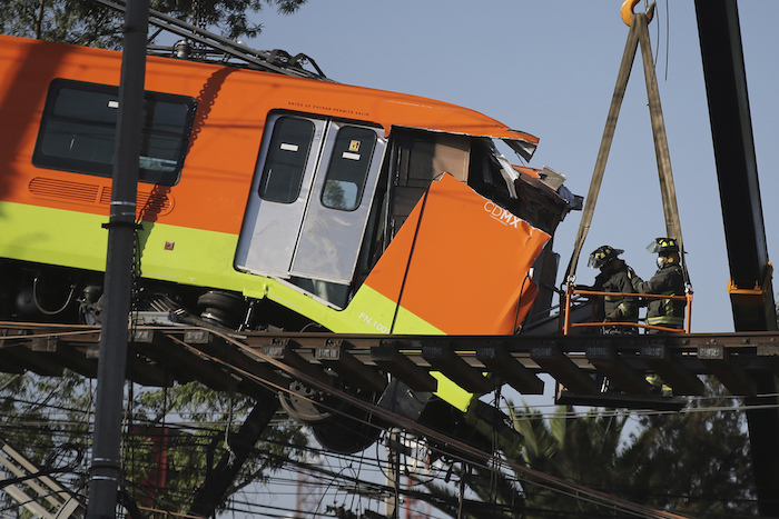 Bomberos trabajando para descolgar hasta el suelo un vagón de Metro que quedó suspendido en un tramo elevado del Metro, en Ciudad de México, el martes 4 de mayo de 2021.
