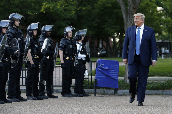 En esta foto de archivo del 1 de junio de 2020, el entonces Presidente Donald Trump pasa frente a la policía en el parque Lafayette después de posar en el exterior de la iglesia de San Juan al otro lado de la plaza de la Casa Blanca, Washington.