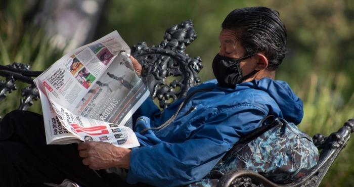 Hombre lee el periódico.