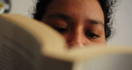 Una joven realiza una lectura en una biblioteca de la Ciudad de México.