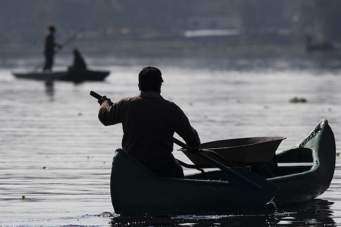 """Un agricultor lleva una carretilla en su canoa mientras rema hasta su granja flotante, conocida como """"chinampa"""", en Xochimilco, en la Ciudad de México, el 12 de agosto de 2021, mientras la capital mexicana se prepara para conmemorar el 500 aniversario de la caída de la capital azteca, Tenochtitlan."""
