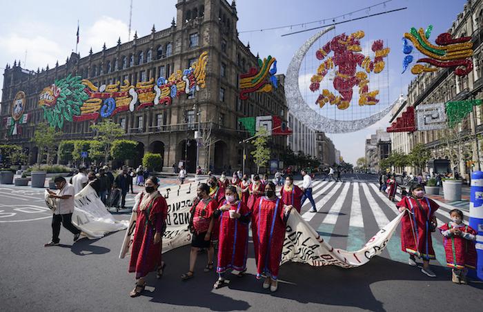 Indígenas triquis, originarios del estado de Oaxaca pero que viven en la Ciudad de México, protestan bajo una imagen de la diosa precolombina de la luna, Coyolxauhqui, para que se les permita vender sus productos cerca de la principal plaza de la capital, el Zócalo, el 9 de agosto de 2021.