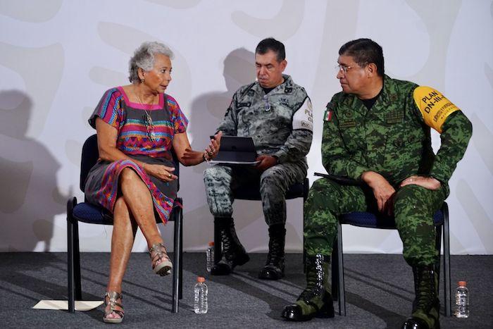 """Olga Sánchez Cordero, entonces Secretaria de Gobernación, conversa con Luis Cresencio Sandoval, Secretario de la Defensa Nacional, durante la """"mañanera"""" de hace unos días en Puerto Vallarta."""