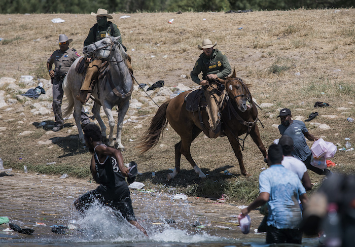 Agentes a caballo de la Oficina de Aduanas y Protección Fronteriza de Estados Unidos tratan de impedir que migrantes crucen el río Bravo desde Ciudad Acuña, México, a Del Río, Texas, el 19 de septiembre de 2021.