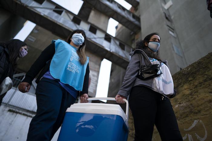 Las enfermeras llevan una hielera con dosis de la vacuna Sinopharm contra la COVID-19 en el barrio Fuerte Apache en la provincia de Buenos Aires, Argentina, el miércoles 18 de agosto de 2021.