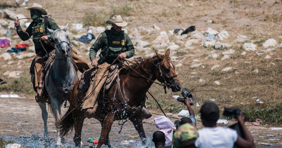 Guardias fronterizos a caballo tratan de impedir el paso de migrantes que cruzan el río Bravo desde Ciudad Acuña, México, a Del Río, Texas, 19 de setiembre de 2021.