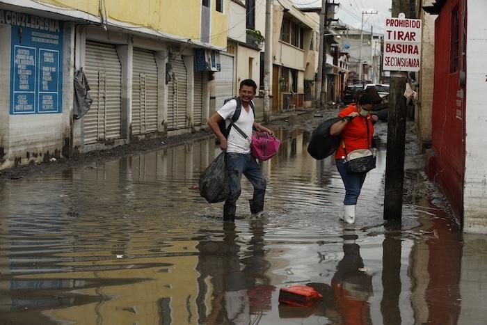 Personas rescatan sus pertenencias luego de una inundación producida por fuertes lluvias, el 9 de septiembre de 2021, en el municipio de Tula, en Hidalgo (México).