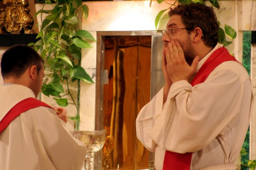 Priest covering his mouth.