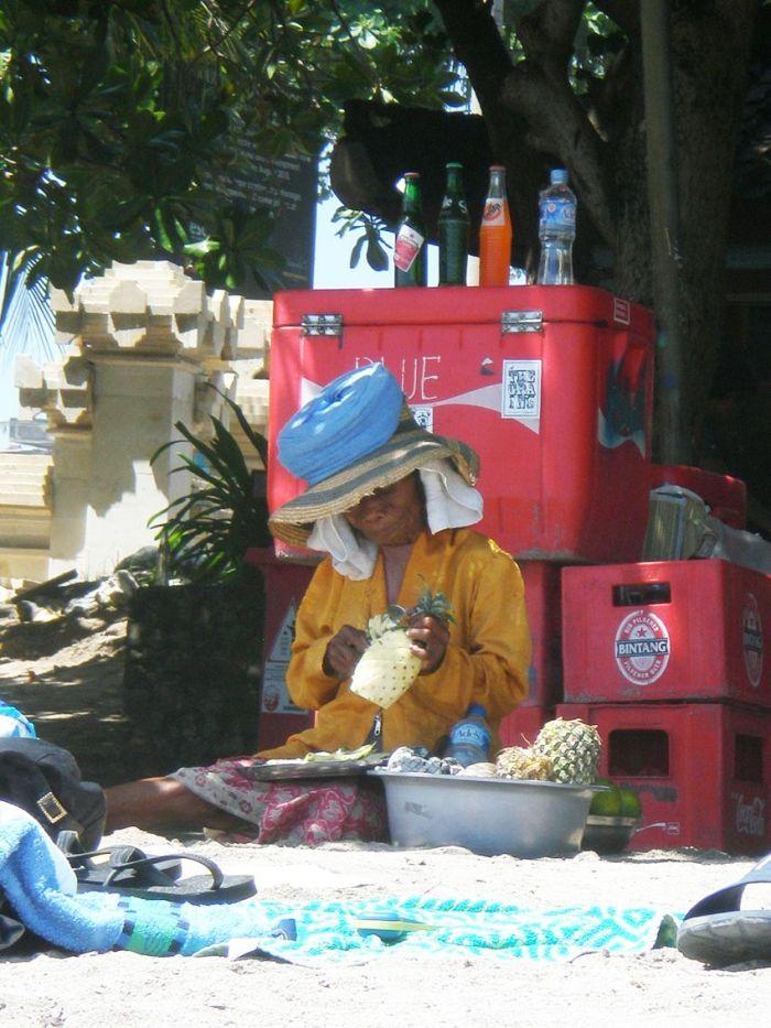 Mujer cortando piña/ananás en la playa de Kuta, Bali, Indonesia - Sinmapa.net