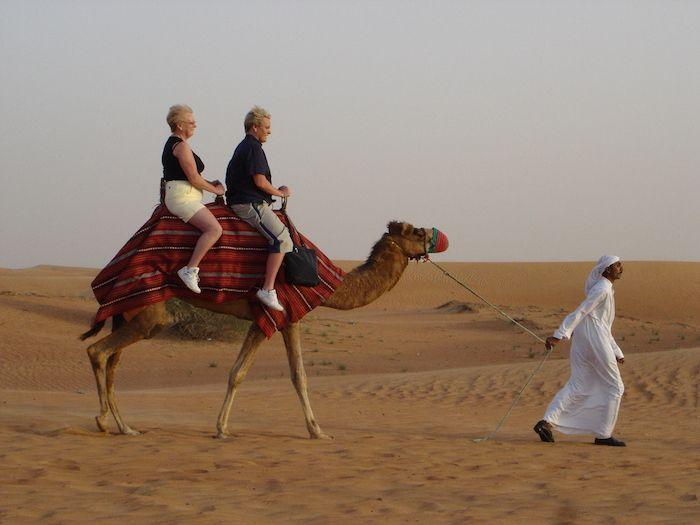 Dos turistas atravesando el desierto sobre un pobre camello