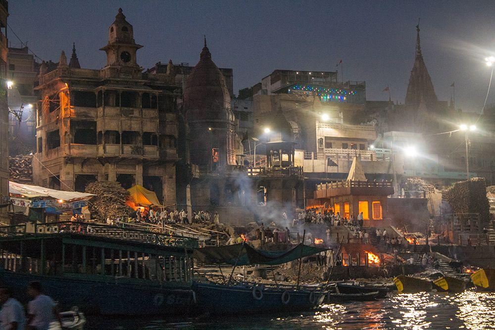 Ghat crematorio principal de noche visto desde una pequeña embarcación en el río Ganges