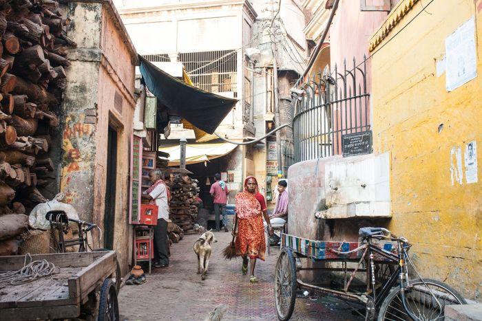 Mujer caminando por las calles traseras del crematorio, rodeada de toneladas de madera listas para los rituales funerarios
