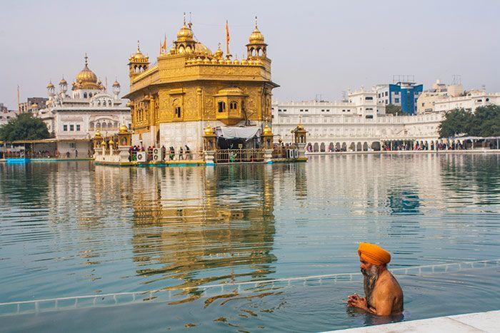 Un sij dándose un baño de purificación en el lago artificial.