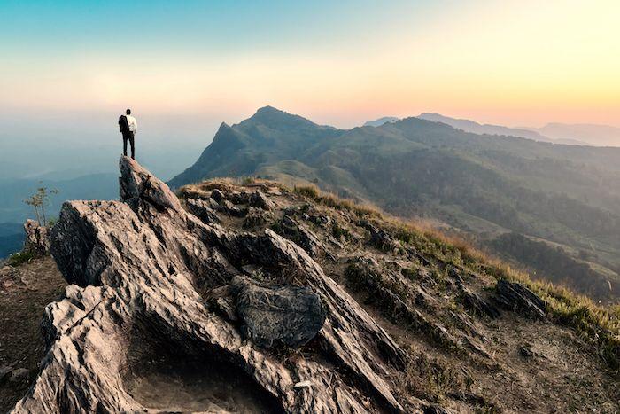 Hombre parado en la cima del mundo vía Shutterstock